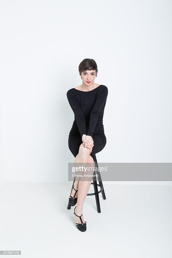 actress sitting on stool