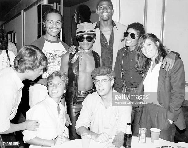 Actress Tatum O'Neal and actor Dan Aykroyd sit at a table and pose fora portrait with pop singer Marlon Jackson basketball player Earvin 'Magic'...