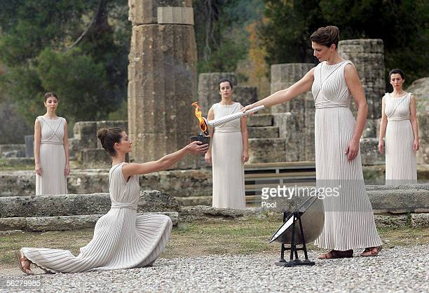 Actress Theodora Siarkou who plays the role of high priestess gives the flame to Avgi Panagiotopoulu using the torch for the Turin 2006 Olympic...