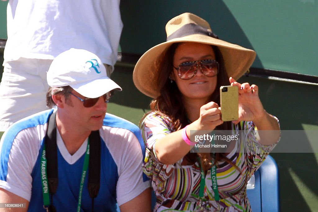 Actress Tia Carrere takes a photo with her smartphone during the men's semifinal match between Tomas Berdych of the Czech Republic and Rafael Nadal of Spain during the 2013 BNP Paribas Open at the Indian Wells Tennis Garden on March 16, 2013 in Indian Wells, California.