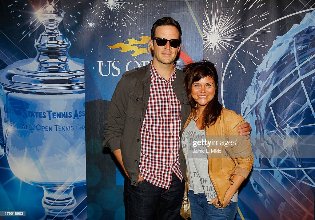Actress Tiffani Amber Thiessen (R) smiles alongside husband and actor <a gi-track='captionPersonalityLinkClicked' href=/galleries/search?phrase=Brady+Smith&family=editorial&specificpeople=223901 ng-click='$event.stopPropagation()'>Brady Smith</a> (L) while attending Day Eleven of the 2013 US Open at the USTA Billie Jean King National Tennis Center on September 5, 2013 in New York City.