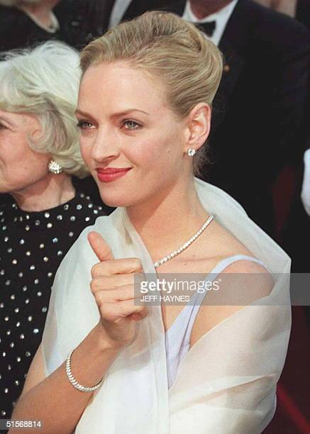Actress Uma Thurman gives a thumb's up as she is greeted by fans as she arrives for the 67th Annual Academy Awards 27 March 1995 in Los Angeles...