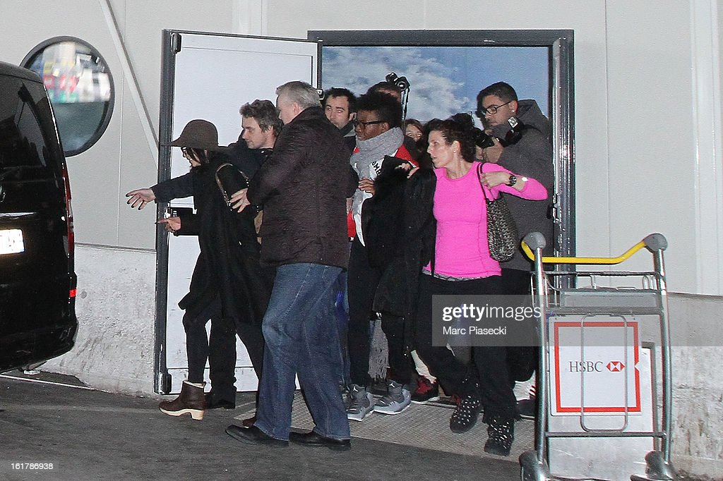 Actress Vanessa Hudgens is led away from fans to a waiting car as she arrives at Roissy airport on February 16, 2013 in Paris, France.