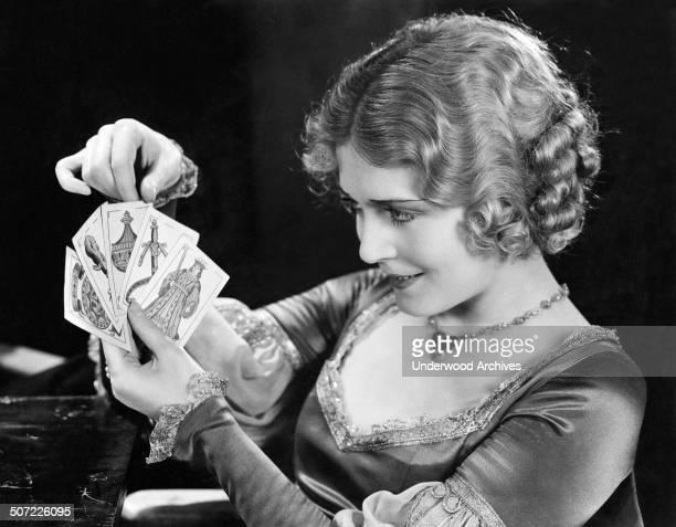 Actress Vilma Banky looks at a hand of tarot cards Hollywood California mid 1920s