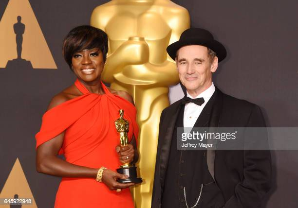 Actress Viola Davis winner of the award for Actress in a Supporting Role for 'Fences' poses with presenter actor Mark Rylance in the press room...