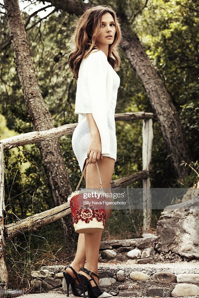 106843-020. Actress Virginie Ledoyen is photographed for Madame Figaro on July 12, 2013 in San Valentino Torio, Italy. Cardigan (Eric Bompard), dress (Chanel), bag (Dolce & Gabbana), shoes (Miu Miu). Make-up by Sisley.