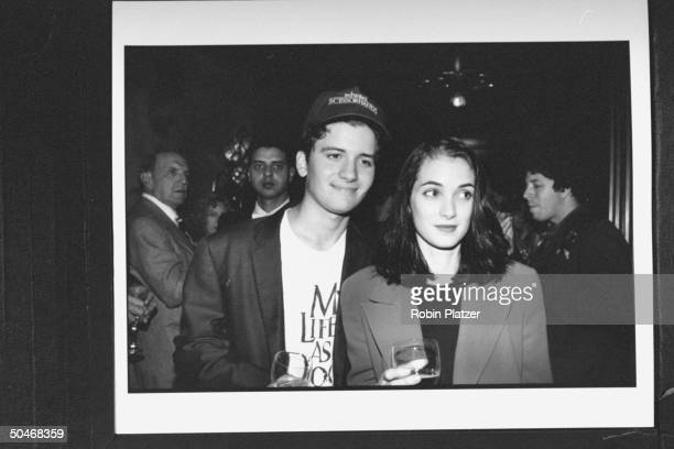 Actress Winona Ryder standing next to unident man wearing Edward Scissorhands cap at premiere of Little Man Tate