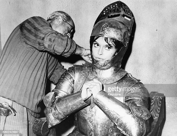 Actress Yvonne Monlaur being helped with her costume a suit of armor on the set of the film 'To Live and Die a Fascist' Rome Italy November 12th 1961