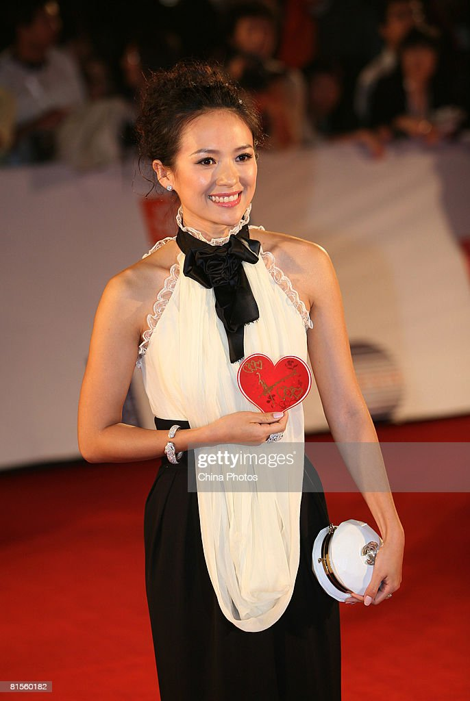 Actress Zhang Ziyi poses on the red carpet holding a heart shape showing support for the earthquake-stricken area of Sichuan, during the opening ceremony of the 11th Shanghai International Film Festival on June 14, 2008 in Shanghai, China. The festival will be held from June 14 to 22.