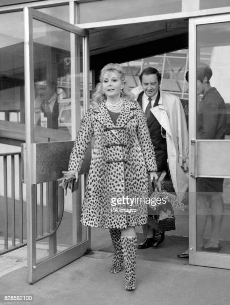 Actress Zsa Zsa Gabor in leopard skin coat and matching high boots as she left Heathrow airport London for Budapest to visit her father's grave...