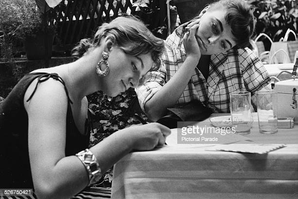 Actresses and siblings Jackie Collins and Joan Collins catching up on correspondence while on location making the film 'Land of the Pharaohs' 1955