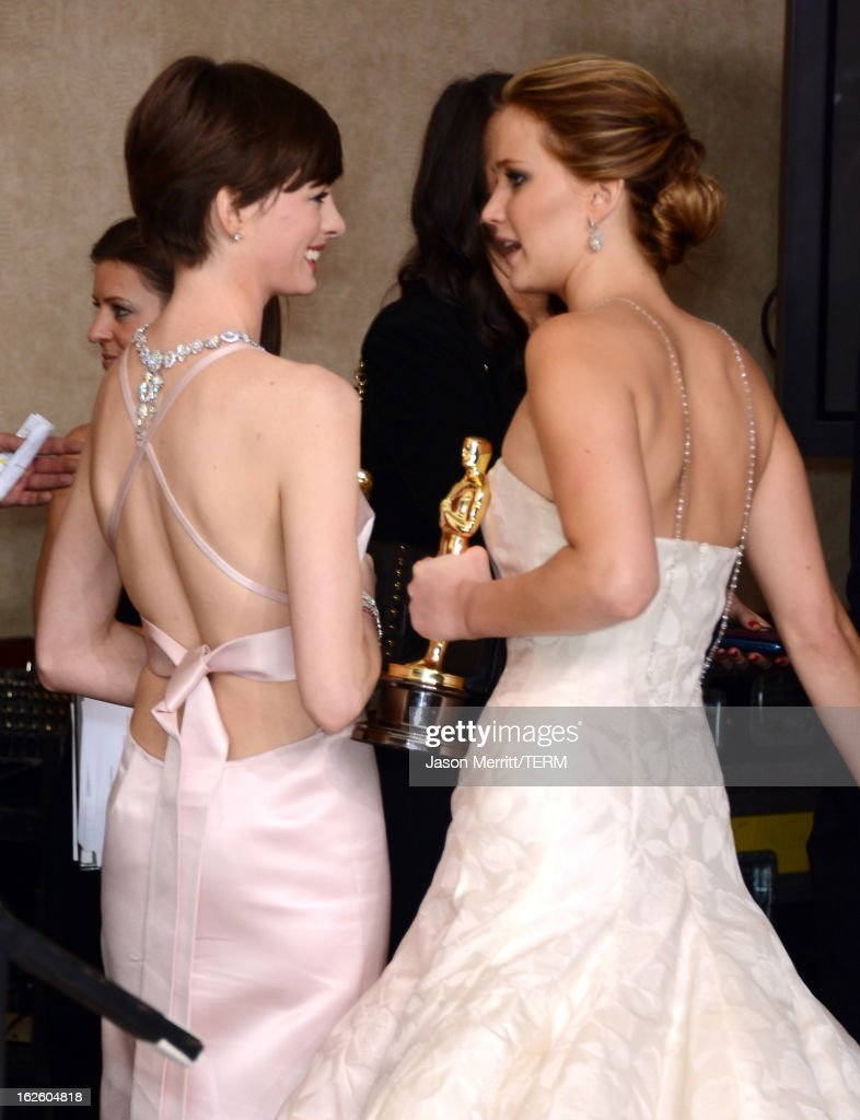 Actresses Anne Hathaway (L), winner of the Best Supporting Actress award for 'Les Miserables,' and Jennifer Lawrence, winner of the Best Actress award for 'Silver Linings Playbook,' walk into the press room during the Oscars held at Loews Hollywood Hotel on February 24, 2013 in Hollywood, California.