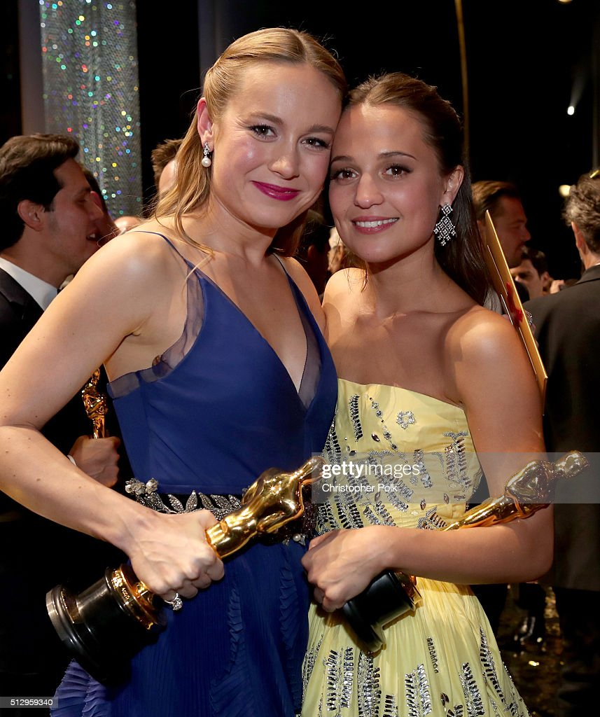 Actresses Brie Larsen (L) and Alicia Vikander backstage at the 88th Annual Academy Awards at Dolby Theatre on February 28, 2016 in Hollywood, California.