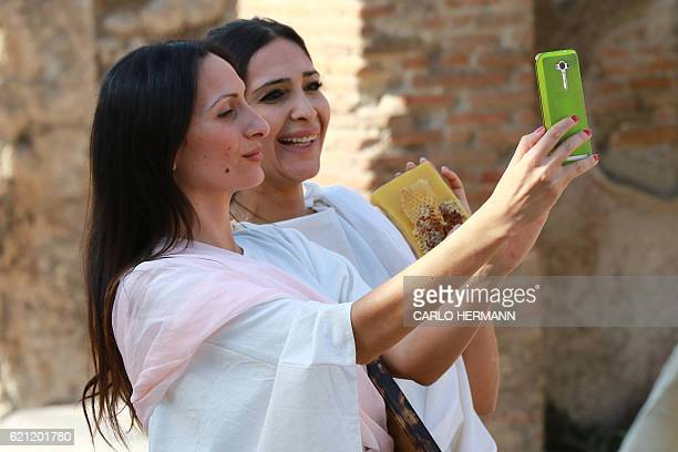 Actresses dressed as ancient Romans pose for a selfie on November 5 during the Eatstory exibition organized by Italian farmer union Coldiretti in the...