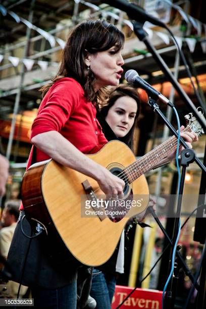 Actresses Elizabeth McGovern and Michelle Dockery of Sadie The Hotheads perform on stage at Leadenhall Market on July 6 2010 in London United Kingdom...