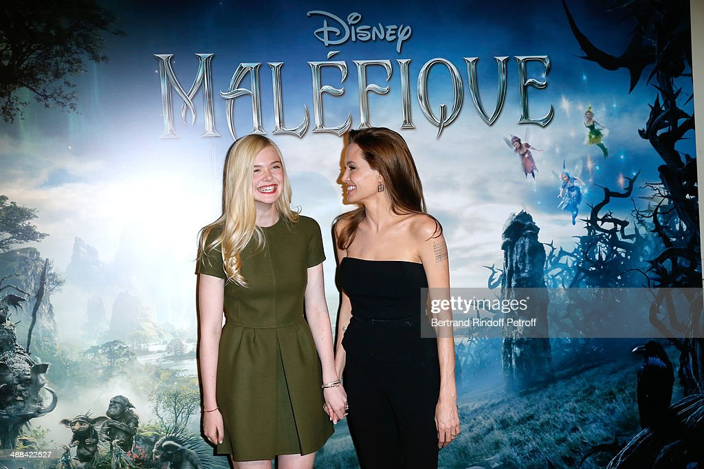 Actresses Elle Fanning and Angelina Jolie (wearing outfit Ralph Lauren, earings Robert Procop) attend the 'Maleficent' Paris Photocall, held at Hotel Bristol on May 6, 2014 in Paris, France.