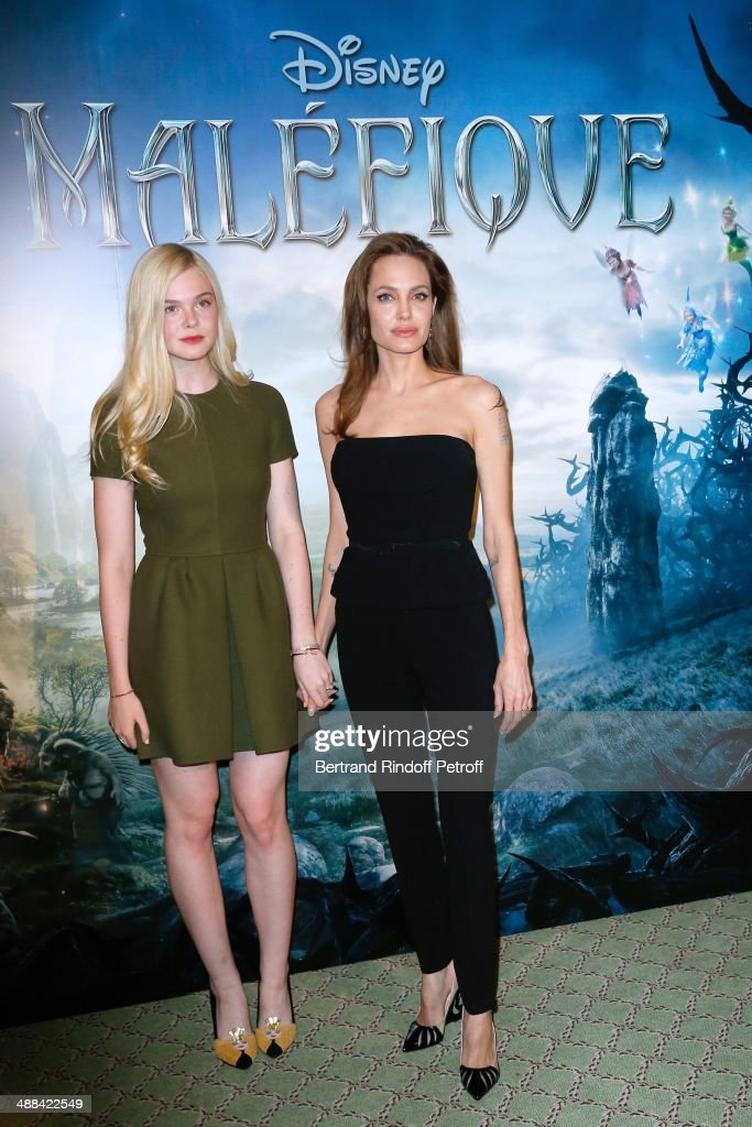 Actresses Elle Fanning and Angelina Jolie (wearing outfit Ralph Lauren, Shoes Christian Louboutin, earings Robert Procop) attend the 'Maleficent' Paris Photocall, held at Hotel Bristol on May 6, 2014 in Paris, France.
