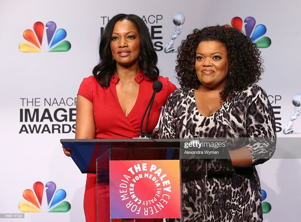 Actresses Garcelle Beauvais and Yvette Nicole-Brown speak at the podium onstage at the 44th NAACP Image Awards Nominations Announcement Press Conference at The Paley Center for Media on December 11, 2012 in Beverly Hills, California.