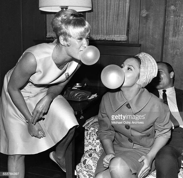 Actresses Hope Holiday and Darbi Winters pose as they have a bubble gum bet during a party in Los AngelesCA