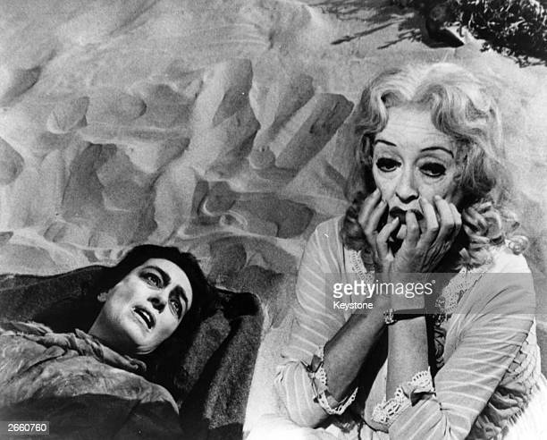 Actresses Joan Crawford and Bette Davis lie on the sand in a scene from the film 'Whatever Happened to Baby Jane' directed by Robert Aldrich