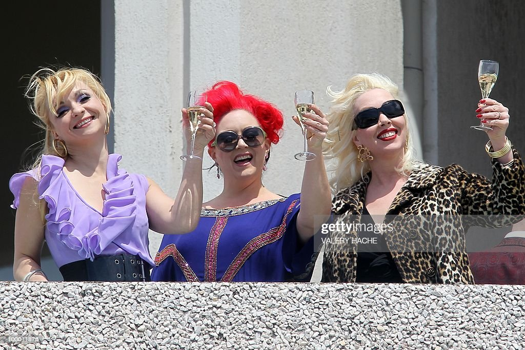 Actresses Julie Atlas Muz, Dirty Martini and Mimi Le Meaux playing in the film 'On Tour' drink champagne on a terasse at the 63rd Cannes Film Festival on May 15, 2010 in Cannes.