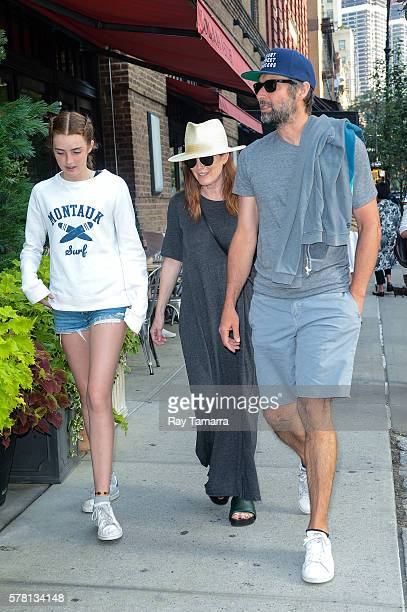 Actresses Liv Freundlich Julianne Moore and director Bart Freundlich walk in Tribeca on July 20 2016 in New York City