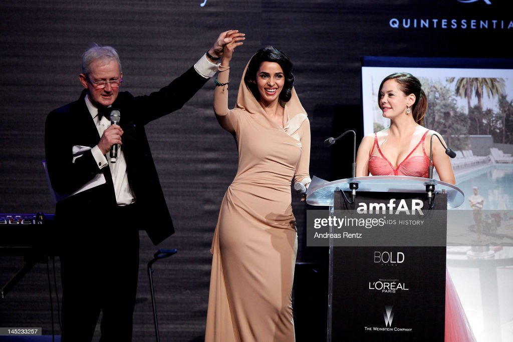 Actresses Mallika Sherawat and Rose McGowan speak onstage during the 2012 amfAR's Cinema Against AIDS during the 65th Annual Cannes Film Festival at Hotel Du Cap on May 24, 2012 in Cap D'Antibes, France.