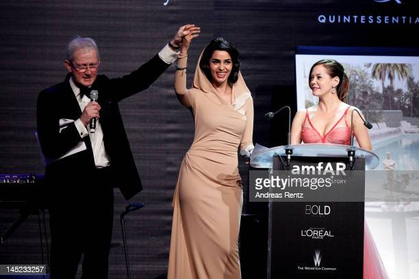 Actresses Mallika Sherawat and Rose McGowan speak onstage during the 2012 amfAR's Cinema Against AIDS during the 65th Annual Cannes Film Festival at...