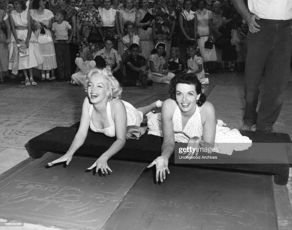 Actresses Marilyn Monroe {L and Jane Russell put their handprints in wet cement at Grauman's Chinese Theater to promote their latest film 'Gentlemen...