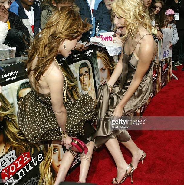Actresses MaryKate Olsen and Ashley Olsen hold their skirts at the gala premiere of 'New York Minute' during the 2004 Tribeca Film Festival at...