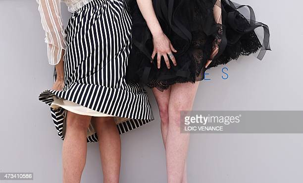 US actresses Parker Posey and Emma Stone hold their skirts down during a photocall for the film 'Irrational Man' at the 68th Cannes Film Festival in...