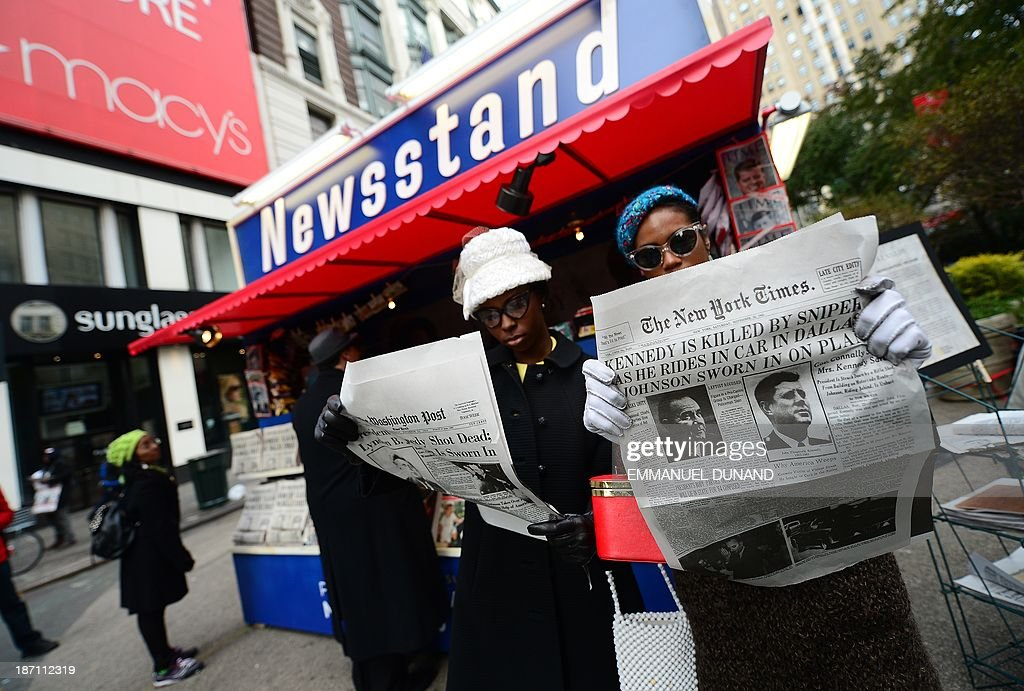 Actresses read newspapers reproductions announcing US president John F. Kennedy's assassination during an act to promote the upcoming 'Killing Kennedy-The Full Story Of The Murder Of JFK' television show, in New York, on November 6, 2013. The show which will air on National Geographic channel on November 10, 2013. Kennedy was killed on November 22, 1963 in Dallas, Texas.