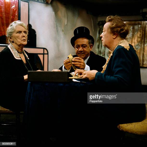 Actresses Sybil Thorndike and Athene Seyler sit at a table counting pound notes with the actor Sid James in a scene from the television drama...