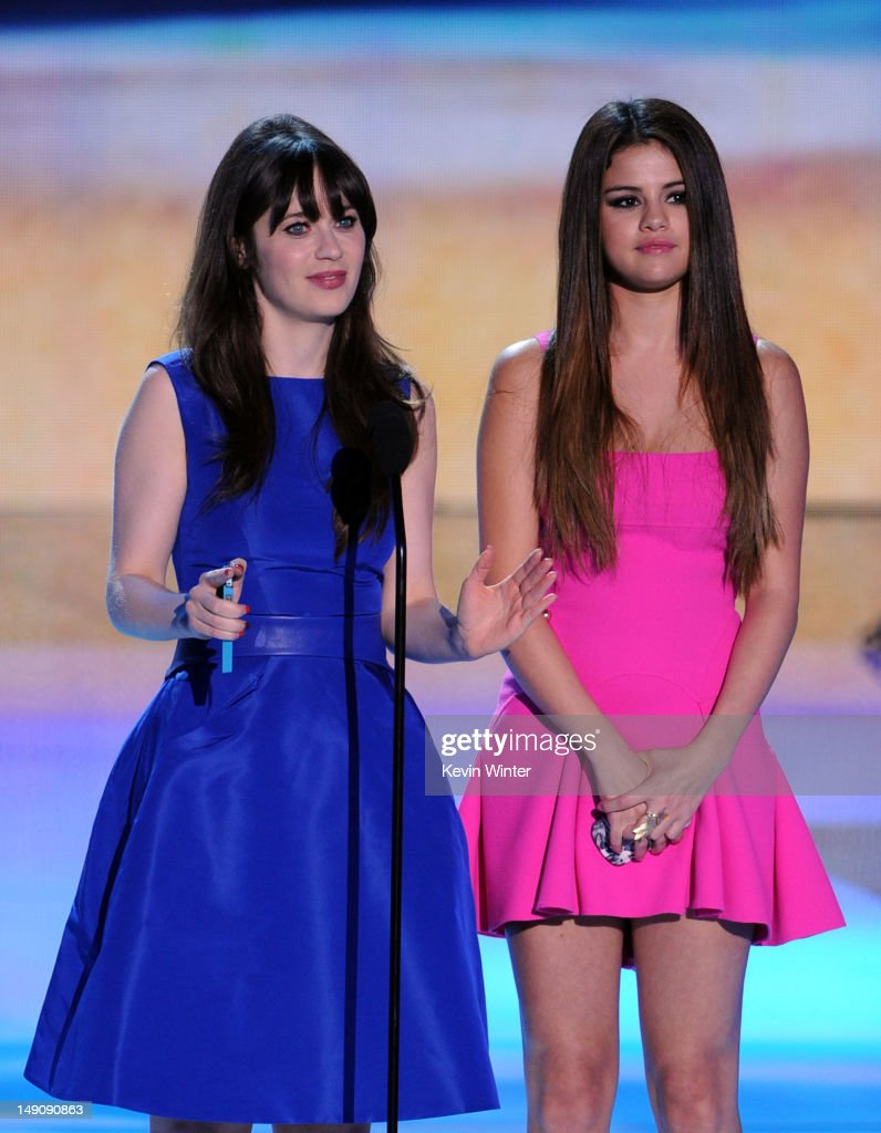 Actresses Zooey Deschanel (L) and Selena Gomez speak onstage during the 2012 Teen Choice Awards at Gibson Amphitheatre on July 22, 2012 in Universal City, California.