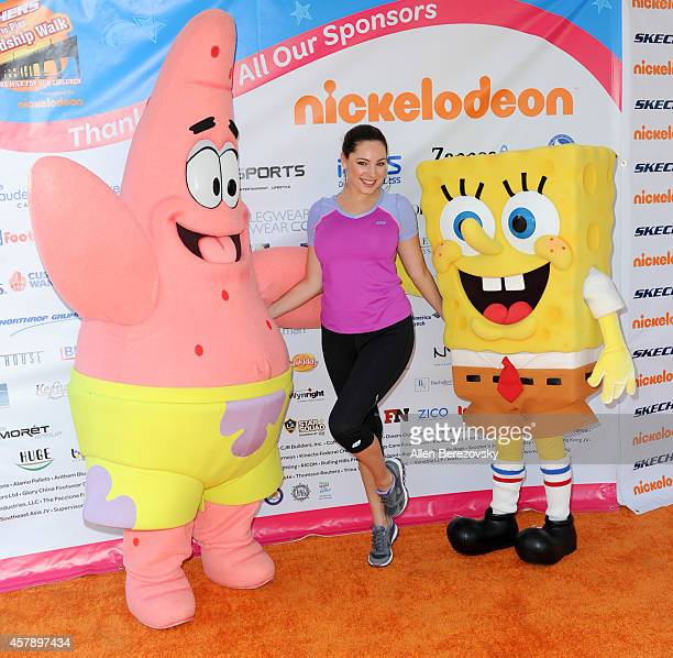 Actress/model Kelly Brook poses for pictures with Patrick Star and SpongeBob SquarePants at the Skechers Pier to Pier Friendship Walk at Manhattan...
