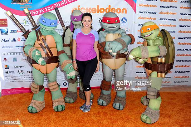 Actress/model Kelly Brook poses with the Ninja Turtles at the Skechers Pier to Pier Friendship Walk at Manhattan Beach Pier on October 26 2014 in...