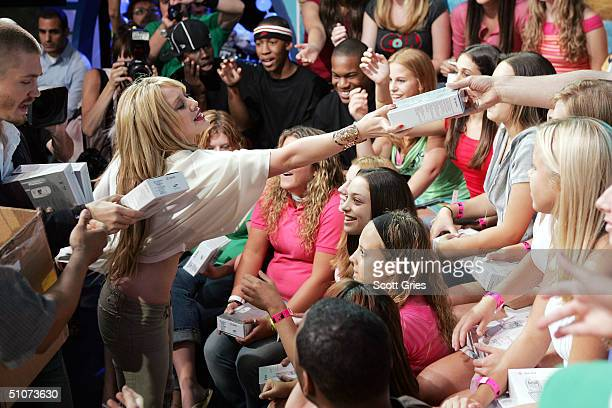 Actress/musician Hilary Duff and actor Chad Michael Murray hand out gifts to the audience on stage during MTV's Total Request Live at the MTV Times...