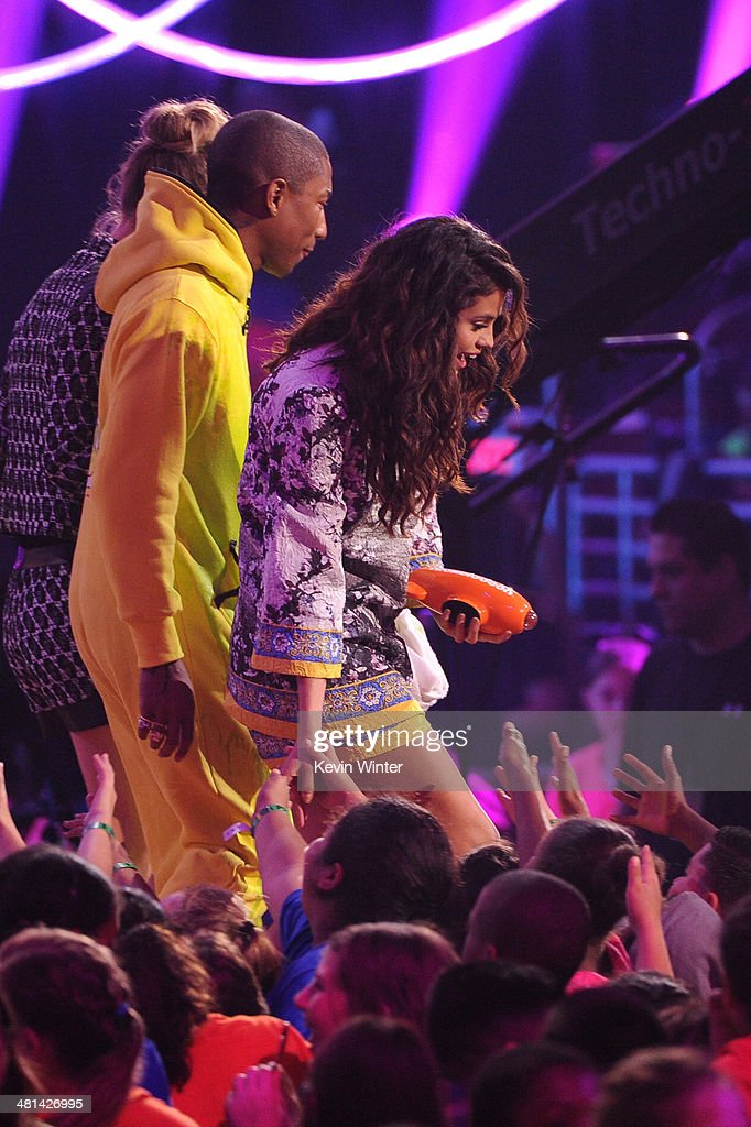 Actress/singer Selena Gomez (R) accepts the award for Favorite Female Singer onstage from musician Pharrell Williams during Nickelodeon's 27th Annual Kids' Choice Awards held at USC Galen Center on March 29, 2014 in Los Angeles, California.