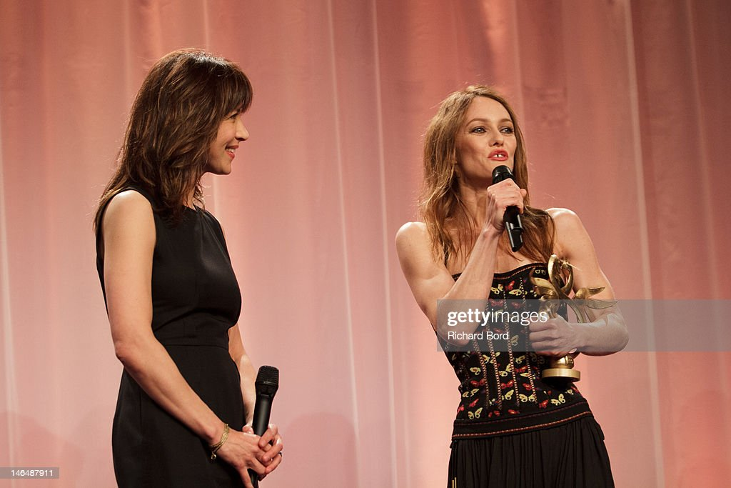 Actress/singer <a gi-track='captionPersonalityLinkClicked' href=/galleries/search?phrase=Vanessa+Paradis&family=editorial&specificpeople=206631 ng-click='$event.stopPropagation()'>Vanessa Paradis</a> (R) is awarded 'Swann d'Honneur' by actress <a gi-track='captionPersonalityLinkClicked' href=/galleries/search?phrase=Sophie+Marceau&family=editorial&specificpeople=220531 ng-click='$event.stopPropagation()'>Sophie Marceau</a> (L) during 26th Cabourg Romantic Film Festival on June 16, 2012 in Cabourg, France.