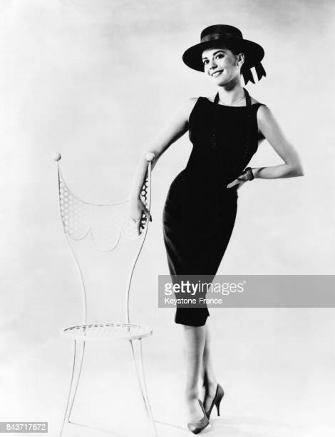 L'actrice américaine Natalie Wood porte une robe et un chapeau élégants à côté d'une chaise aux lignes épurées créée par un designer français circa...
