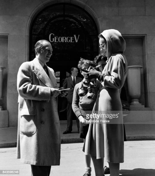 L'actrice américaine Paulette Goddard signe un autographe devant son hôtel Georges V à Paris France en 1946