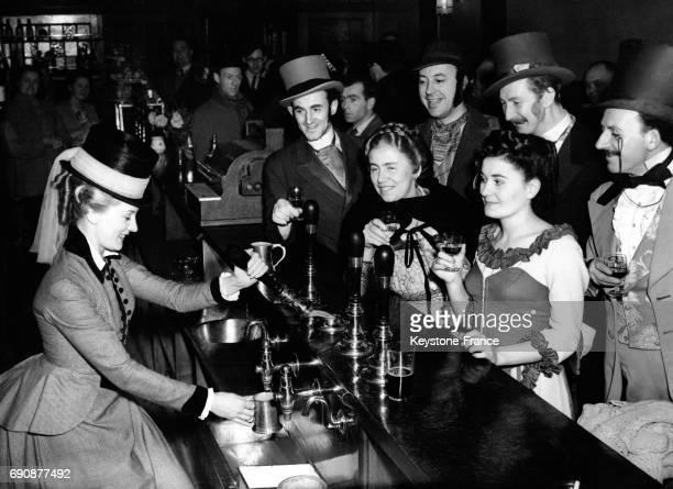 L'actrice Anne Crawford venue au pub 'Ye Whyte Hart' sert des bières aux autres acteurs avec le sourire le 12 novembre 1949 à Londres RoyaumeUni