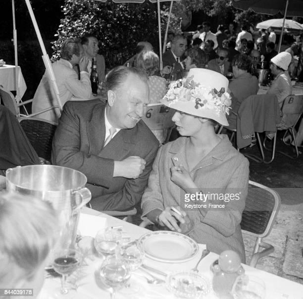 L'actrice italienne Sophia Loren coiffée de son chapeau à fleurs fétiche discute ave l'ambassadeur soviétique Sergueï Vinogradov attablée à une...