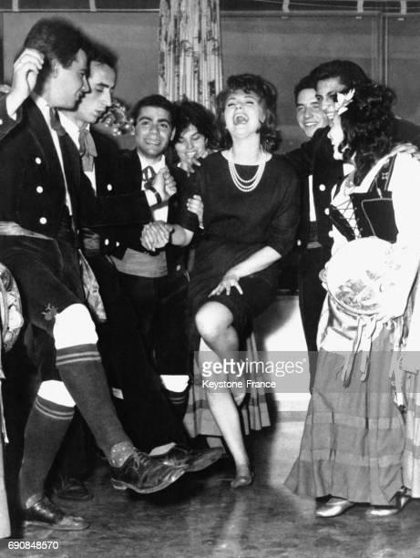 L'actrice italienne Sylva Koscina danse et rit avec une troupe de danseurs folkloriques