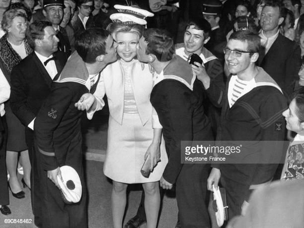 L'actrice italienne Sylva Koscina embrassée par de jeunes marins français à son arrivée au festival de Cannes en France