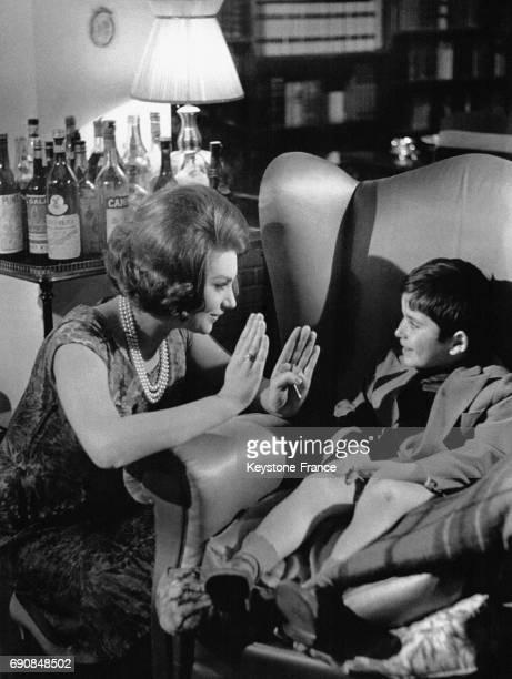 L'actrice italienne Sylva Koscina parle à un enfant assis dans un grand fauteuil