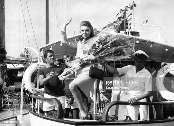L'actrice italienne Sylva Koscina salue depuis un bateau avec une gerbe de fleurs dans les bras
