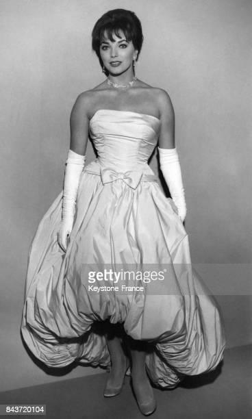 L'actrice Joan Collins vêtue d'une robe de soirée bouffante qu'elle appelle la robe 'aspirateur' arrive à la cérémonie des Oscars à Los Angeles en...