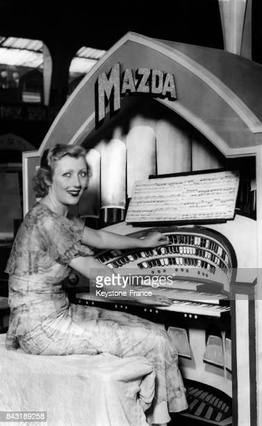 L'actrice Muriel Angela assise près d'un poste radiophonique lors du Radio Show à l'Olympia le 18 août 1932 à Londres RoyaumeUni