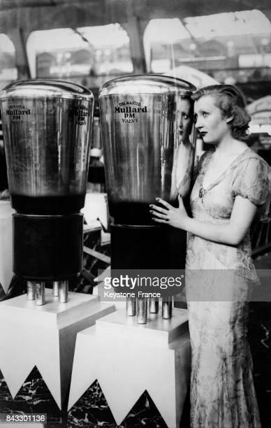 L'actrice Muriel Angels photogaphiée avec deux énormes tubes électroniques pour radio présentés au Salon à Londres RoyaumeUni le 18 août 1932
